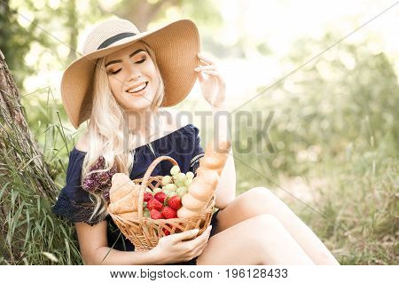 Smiling blonde girl 22-24 year old holding basket ful of fresh food i park. Having picnic in park. Summer season.