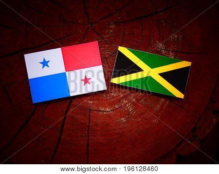 Panamanian Flag With Jamaican Flag On A Tree Stump Isolated