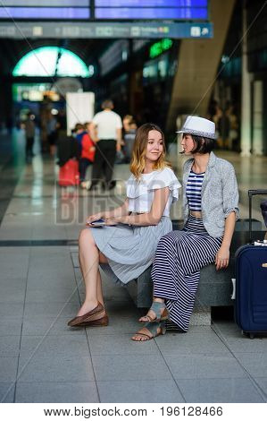 Young women are sitting in the waiting room at the railway station. Next to them is the luggage. The tourists are in a good mood. Summer vacation.