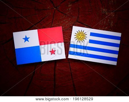 Panamanian Flag With Uruguaian Flag On A Tree Stump Isolated