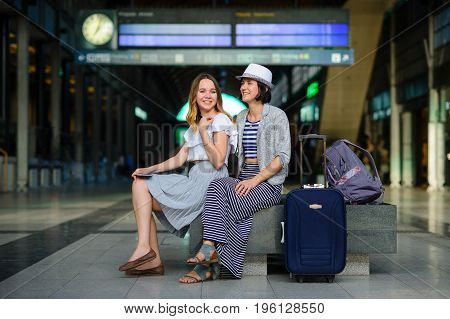 Young women are sitting in the waiting room at the railway station. Next to them is a backpack and a suitcase. The tourists are in a good mood. Summer vacation.