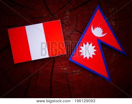 Peruvian Flag With Nepali Flag On A Tree Stump Isolated