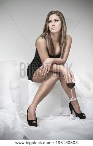 Woman sitting with a glass of wine in a white paperchaos