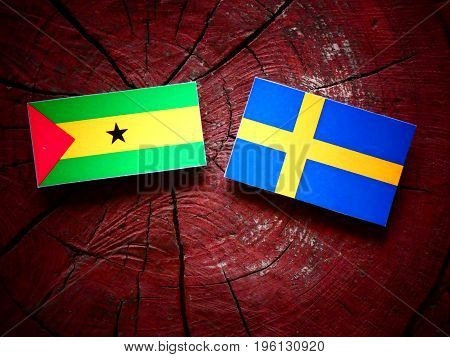Sao Tome And Principe Flag With Swedish Flag On A Tree Stump Isolated