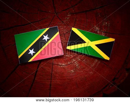 Saint Kitts And Nevis Flag With Jamaican Flag On A Tree Stump Isolated