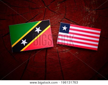 Saint Kitts And Nevis Flag With Liberian Flag On A Tree Stump Isolated