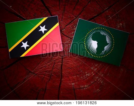 Saint Kitts And Nevis Flag With African Union Flag On A Tree Stump Isolated
