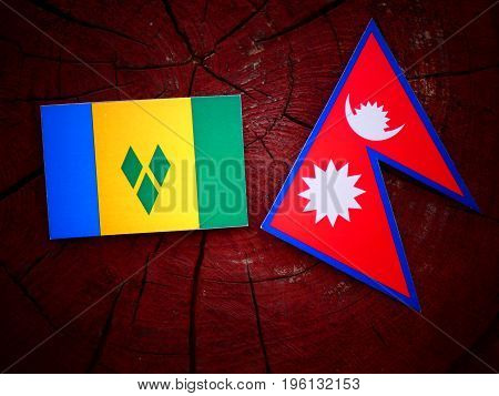 Saint Vincent And The Grenadines Flag With Nepali Flag On A Tree Stump Isolated