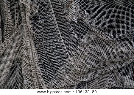 old fishing net hangs on the wall background