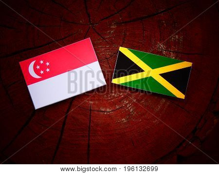 Singaporean Flag With Jamaican Flag On A Tree Stump Isolated
