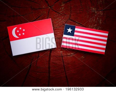 Singaporean Flag With Liberian Flag On A Tree Stump Isolated