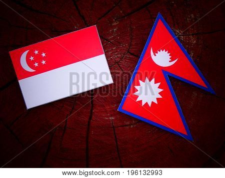 Singaporean Flag With Nepali Flag On A Tree Stump Isolated