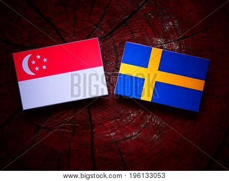 Singaporean Flag With Swedish Flag On A Tree Stump Isolated