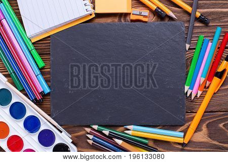Back to school. Different stationery - pencils pen note erazer paint and empty slate board on wooden background. Top view. Place for text.