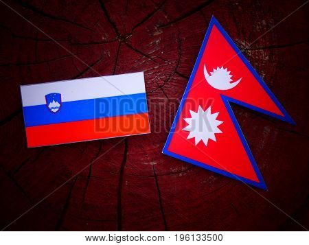 Slovenian Flag With Nepali Flag On A Tree Stump Isolated
