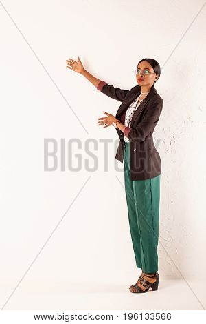 African american woman in business clothes standing on a white background and talking about something.