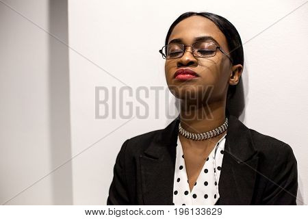 Attractive business woman with her eyes closed standing by the wall.