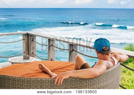 Young surfer relaxing in lounge on roof veranda with beautiful tropical sea view. Positive man look at ocean surf enjoy vacation. Healthy lifestyle people on family summer beach holiday.