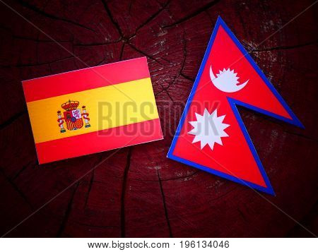 Spanish Flag With Nepali Flag On A Tree Stump Isolated