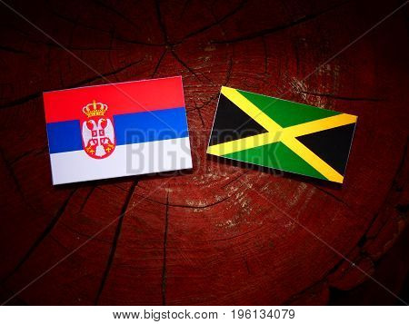 Serbian Flag With Jamaican Flag On A Tree Stump Isolated
