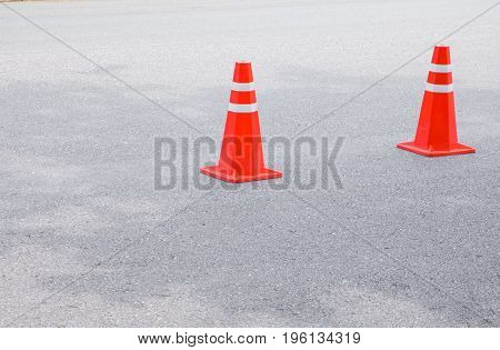 Traffic cone old orange and swath white stripes on the road with copy space