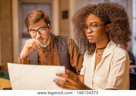 Two young people, african american woman and man, sitting by the table. Woman holding paper with graphics.