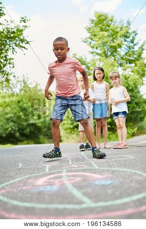 African boy in concentration playing hopscotch with friends
