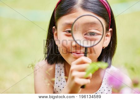 Girl as scientist with magnyfing glass examinating nature