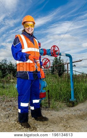 Woman worker in the oilfield near wellhead, wearing orange helmet and work clothes. Industrial site background. Oil and gas concept.