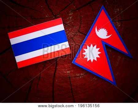 Thai Flag With Nepali Flag On A Tree Stump Isolated