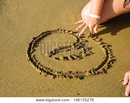 Little girl writting AT symbol in the sand holiday message email sign in wet sand