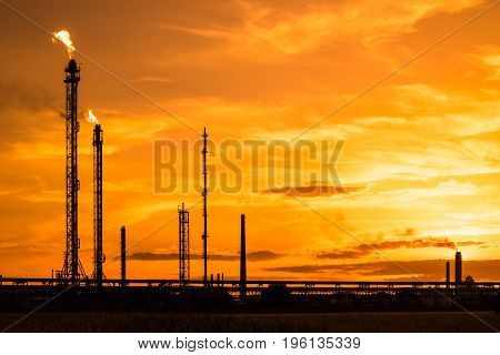Petrochemical factory at sunset refinery factory silhouette at orange sunset burning chimney