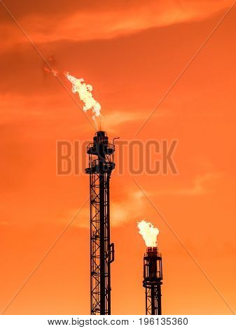 Refinery chimney with fire at orange sunset detail