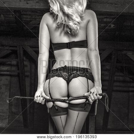 Sexy blonde woman in underwear holding whip behind ass bdsm black and white