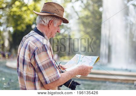 Senior tourist man searching for destination on map during trip