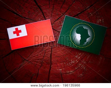 Tongan Flag With African Union Flag On A Tree Stump Isolated