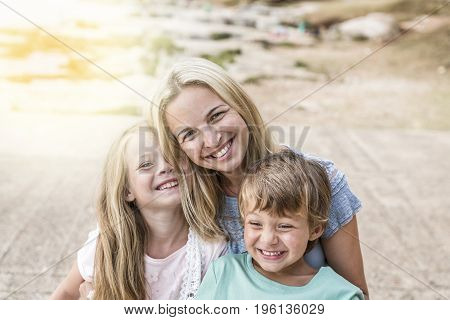 Mother With Children Cuddling On The Beach