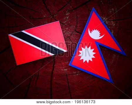 Trinidad And Tobago Flag With Nepali Flag On A Tree Stump Isolated