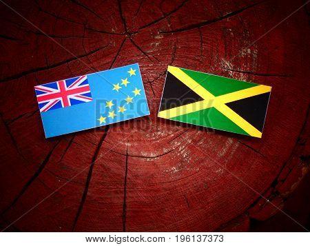 Tuvalu Flag With Jamaican Flag On A Tree Stump Isolated