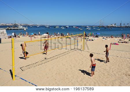 CASCAIS PORTUGAL - JUNE 7 2017: People relaxing on the Praia Ribeira public beach. Cascais is famous and popular summer vacation spot for Portuguese and foreign tourists