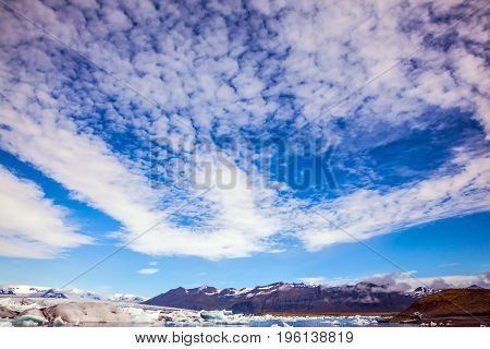 The icebergs and cirrocumulus clouds of lagoon Jokulsarlon, Iceland. The concept of northern extreme tourism
