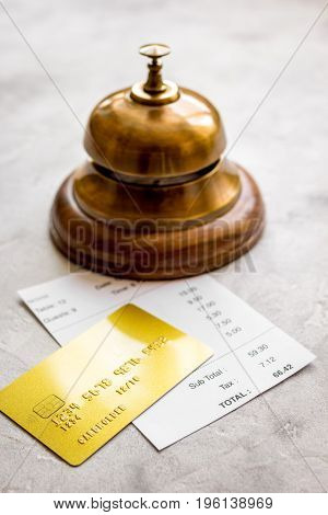 credit card for paying, waiter bell and check on cafe gray stone desk background