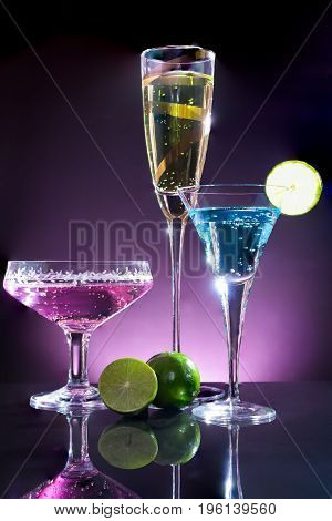 Glasses of blue yellow and purple cocktail with green lime on the bar with dark tone pink background