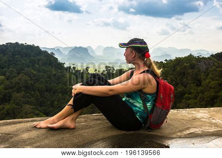 Hiker woman with backpack admires Thailand rain forest, Krabi