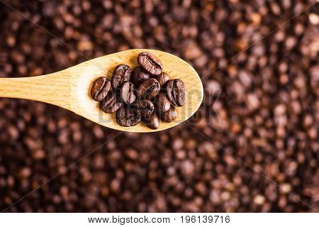 Roasted coffee bean background and texture with wooden spoon selective focus