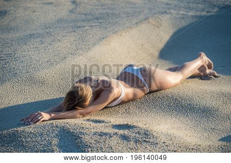 Beautiful sexy woman laying at the beach on her slim belly with arms above her head and face down to the sand