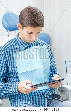 Handsome young man in visit at the dental office. He is sitting on the chair holding a tablet in hands and waiting for dentist. Dentistry