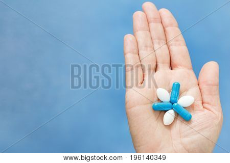 Close-up shot of hand holding blue and white pills in the form like flower. Pills on woman hand