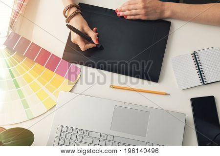 graphic designer using digital drawing tablet at office. top view