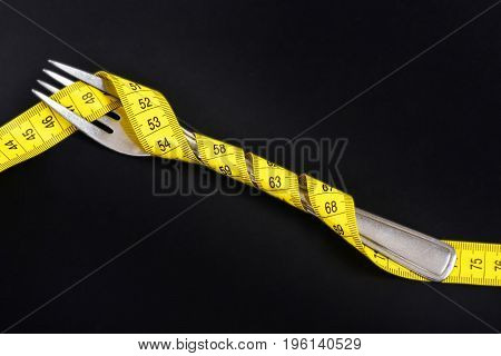 Cutlery item wrapped tight with bright yellow flexible ruler on black background. Concept of diet healthy nutrition and lifestyle slim shape and fit body